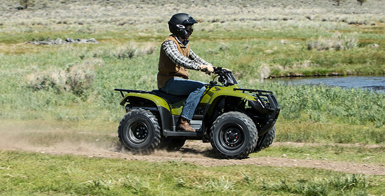 A person riding an ATV across a field