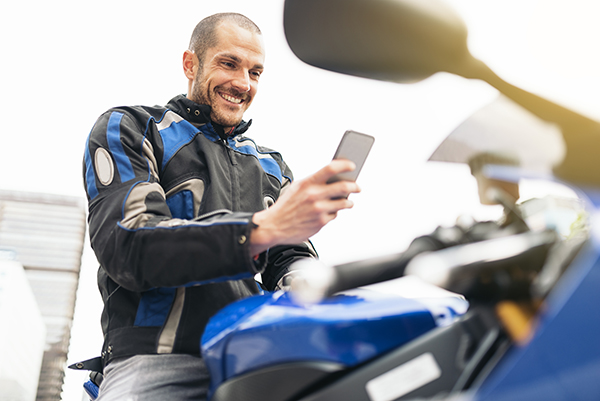 Motorcyclist looking at an iPhone, preparing to use an app.